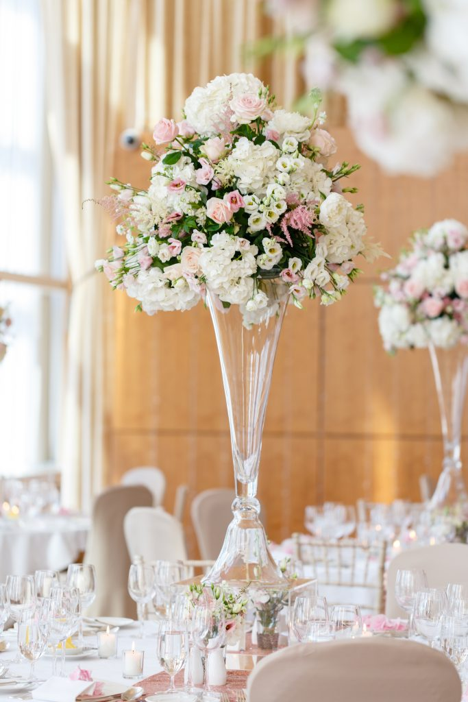 tall table centre in glass vase with mini vases at base .Pink.white