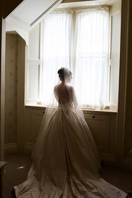 Bride staning in front of a window with a chapel veil