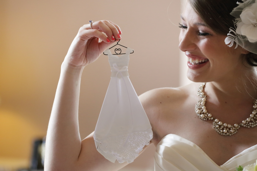 Bride holding a miniature dress