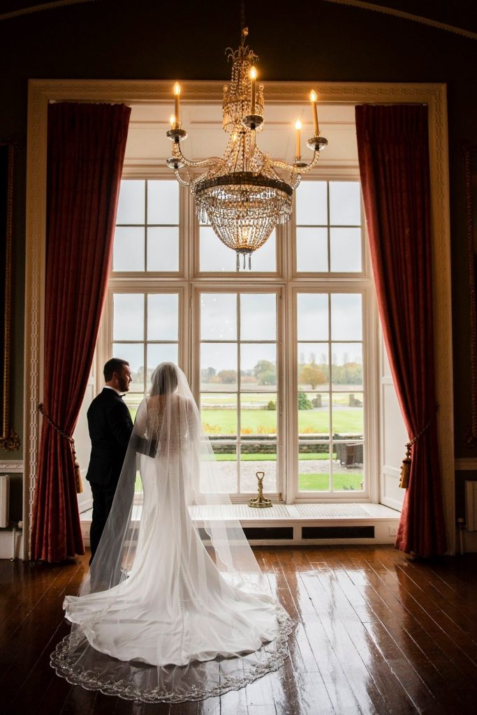Couple in front of window after first look