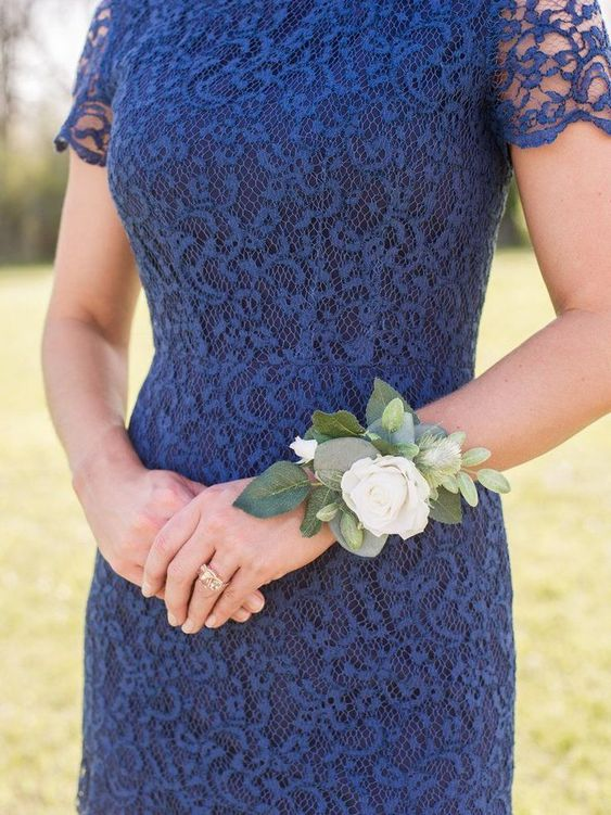 A women wearing a white rose corsage on her wrist.