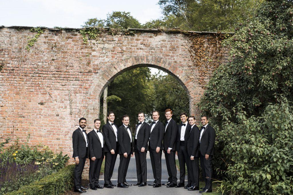 Groom and his groomsmen wearing tuxedos.