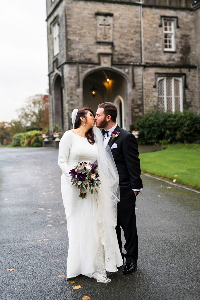 Couple kissing in front of castle