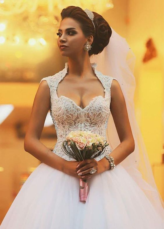 Bride wearing a Queen Anne neckline dress and holding a bouquet