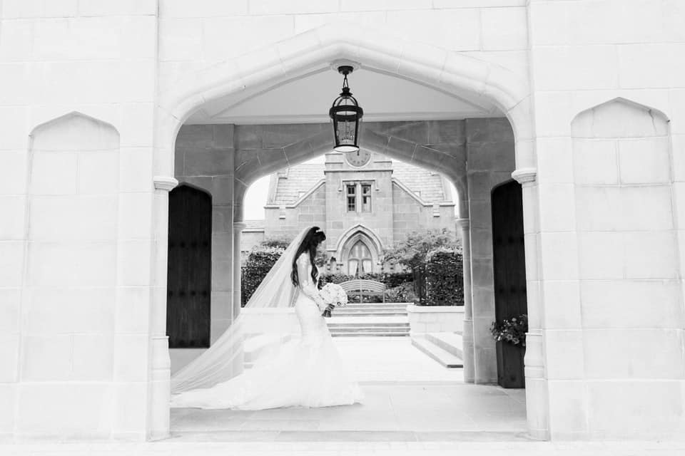 Bride walking under an arch, with a cathedral veil.