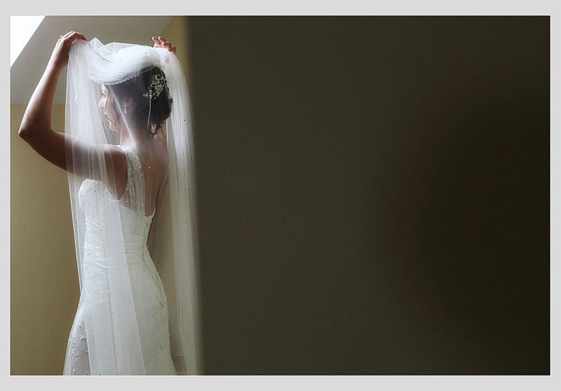 Bride pushing back her veil standing in front of a window