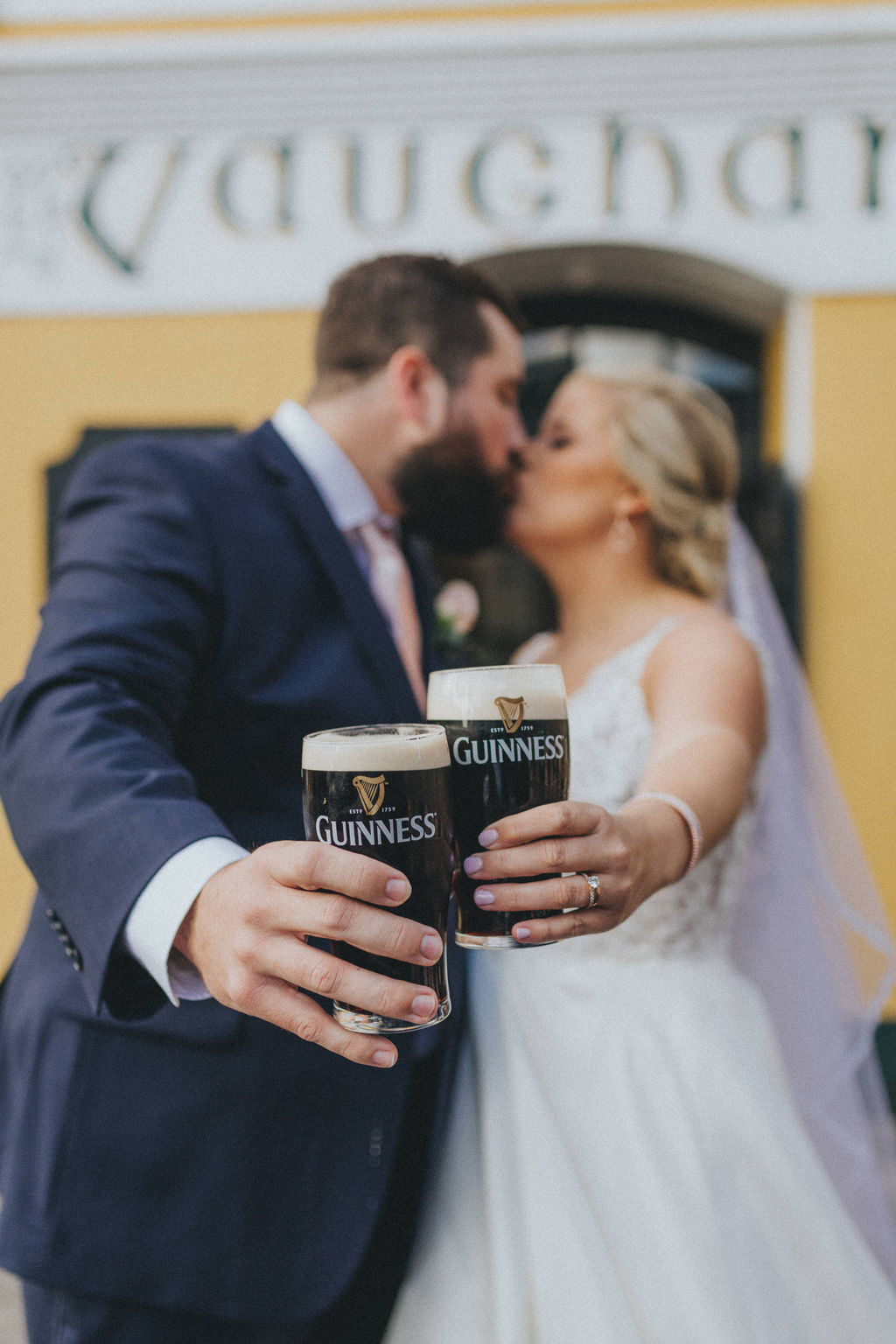 Couple kissing while holding pints of Guinness