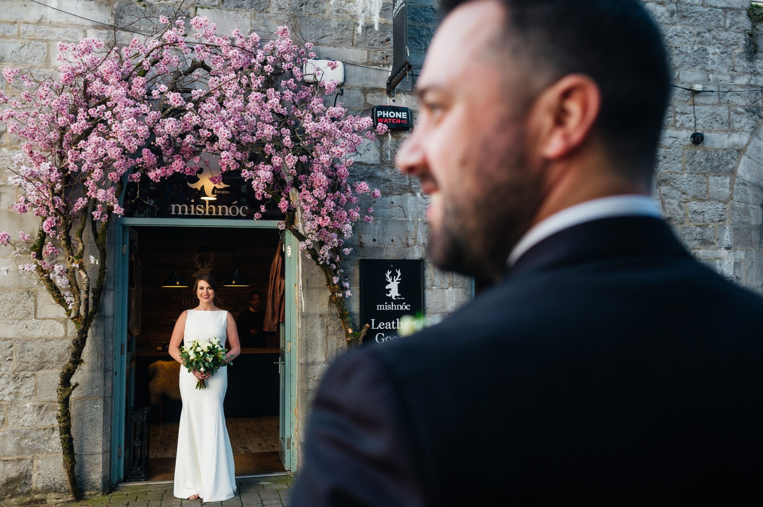 Bride under pink blossom with Groom looking on