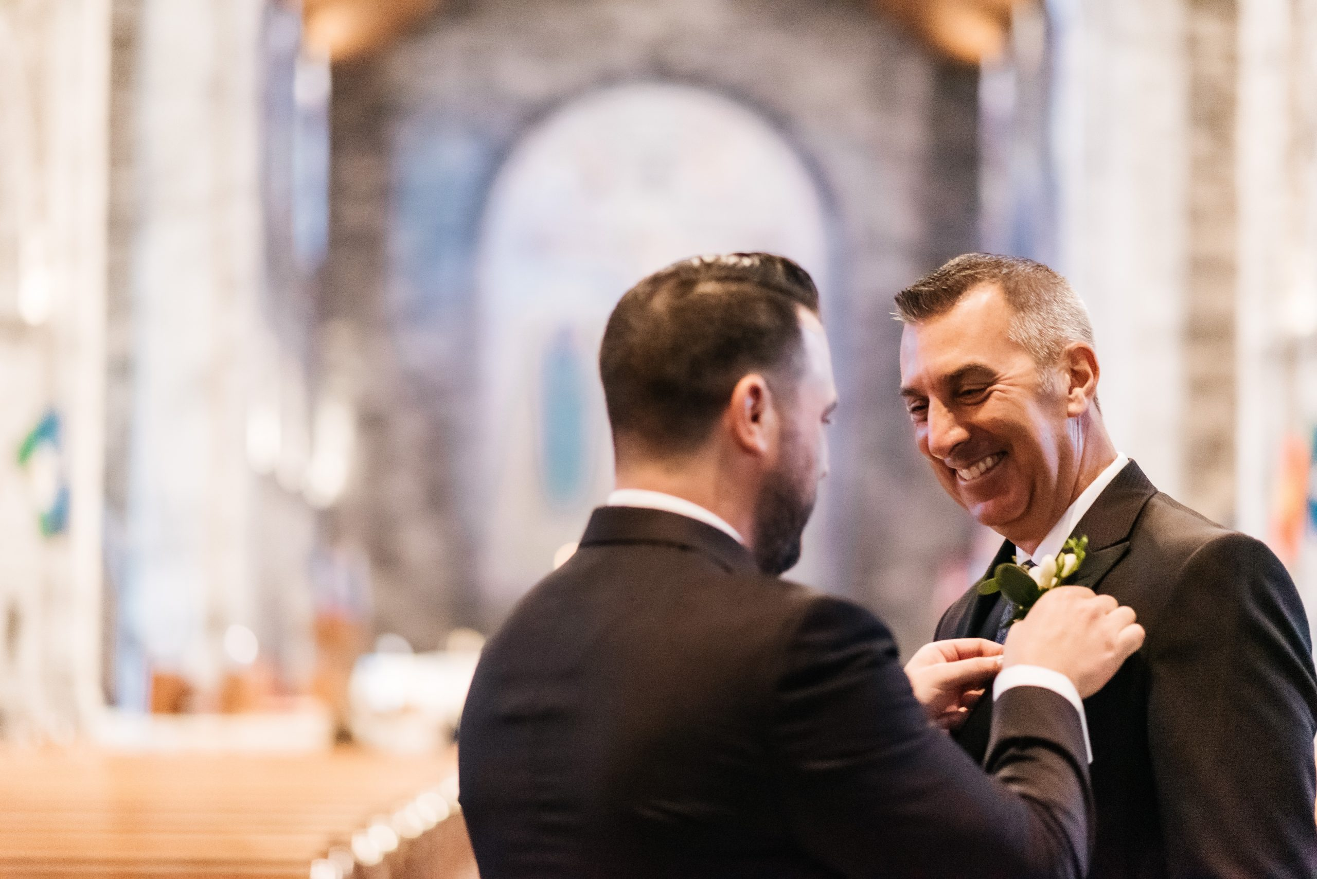 Groom putting on his dad's boutonniere